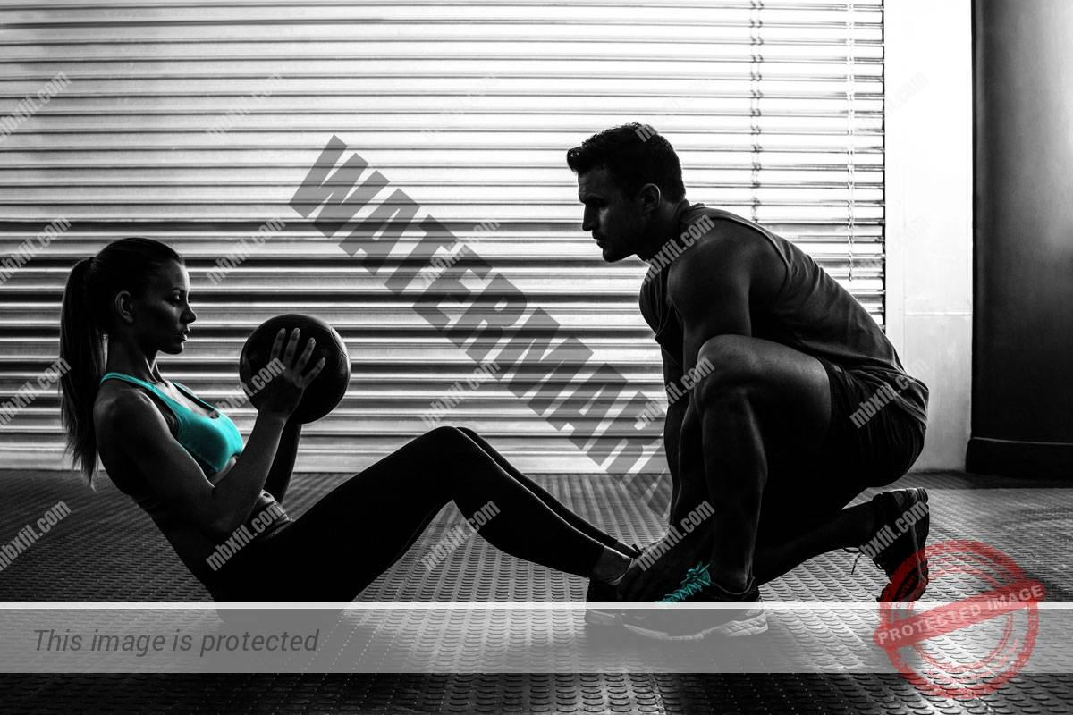 Male personal trainer with fit female client